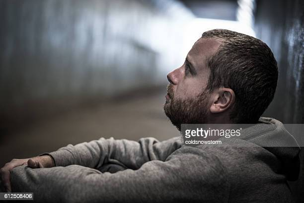 Homeless adult male sitting in subway tunnel begging for money