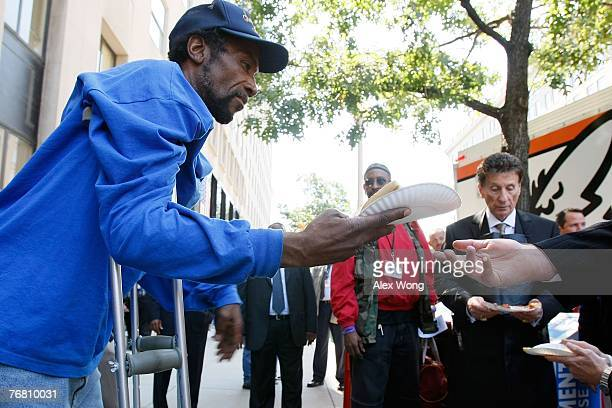 Homeless Army veteran James Alston who served in Vietnam gets a slice of pizza that was handed out from the Little Caesars Love Kitchen a mobile...