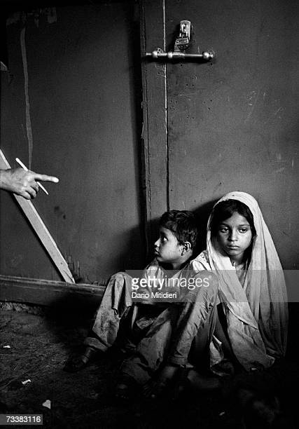 A homeless boy and girl street children huddle on the pavement in front of a padlocked door in 1992 Bombay India Estimated numbers vary from 35000 to...