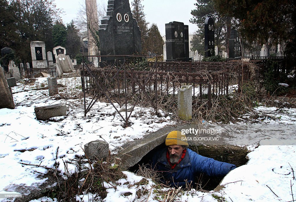 Homeless Bratislav Jovanovic, 43, enters a grave, which he uses as a shelter during winter time at a cemetery in Nis, 200 kilometres south Belgrade, on January 10, 2013. Jovanovic has been homeless for nearly twenty years, since his house was burned down in a fire. The last 15 years he lives in a tomb beside the caskets of his decedents.