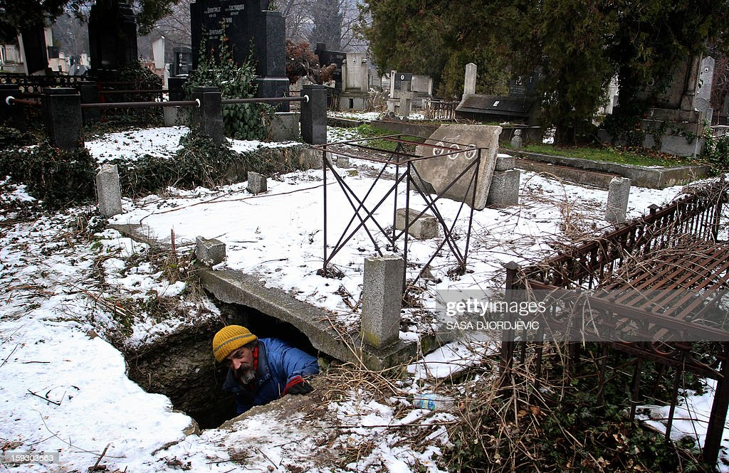 Homeless Bratislav Jovanovic, 43, leaves on January 10, 2013 a grave, he uses as a shelter during winter time at a cemetery in Nis, 200 kilometres south of Belgrade. Jovanovic has been homeless for nearly twenty years, since his house was burned down in a fire. The last 15 years he lives in a tomb beside the caskets of his decedents.