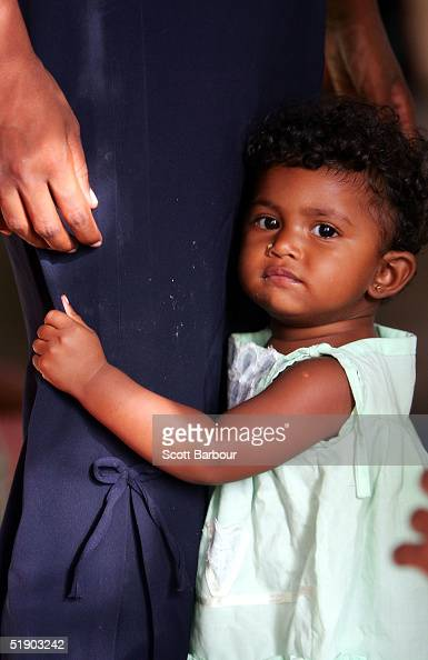 A homeless child clings to its mothers leg at a regugee camp which has been set up in a budhist temple after a massive tsunami wave swept across...