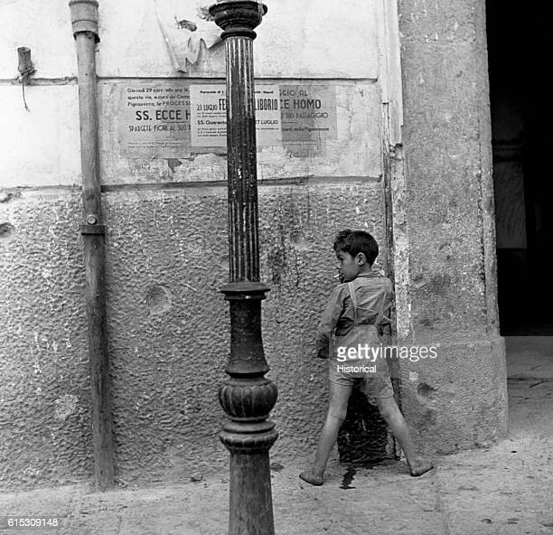 A homeless child urinates on the side of a building while smoking a cigarette during World War II Naples Italy August 1944