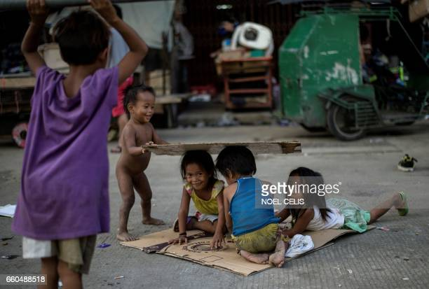 TOPSHOT Homeless children play on a street at Divisoria market in Manila on March 30 2017 / AFP PHOTO / NOEL CELIS