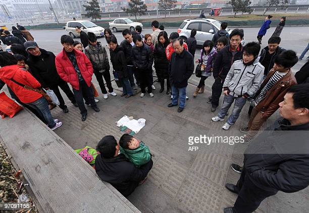A homeless Chinese man attracts a crowd as he offers his sixyearold daughter up for adoption along a street in Beijing on February 25 2010 In China a...