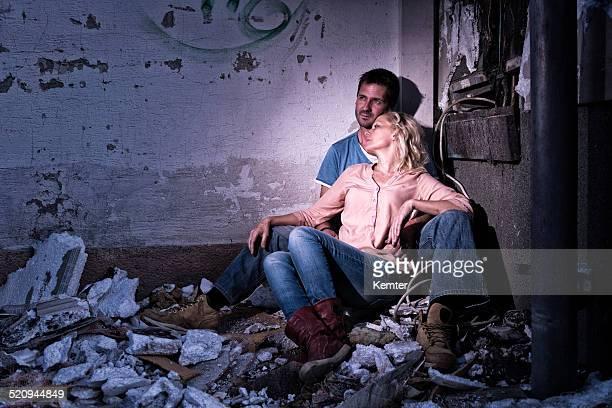 Senzatetto coppia di notte, seduta in un angolo