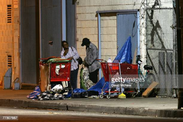 A homeless couple gets up before dawn to dismantle their encampment before businesses open October 12 2007 in the downtown Skid Row area of Los...