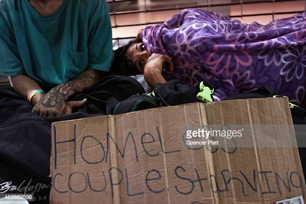 A homeless couple sleep on a Manhattan street on August 22 2014 in New York City According to the Department of Homeless Services the number of...