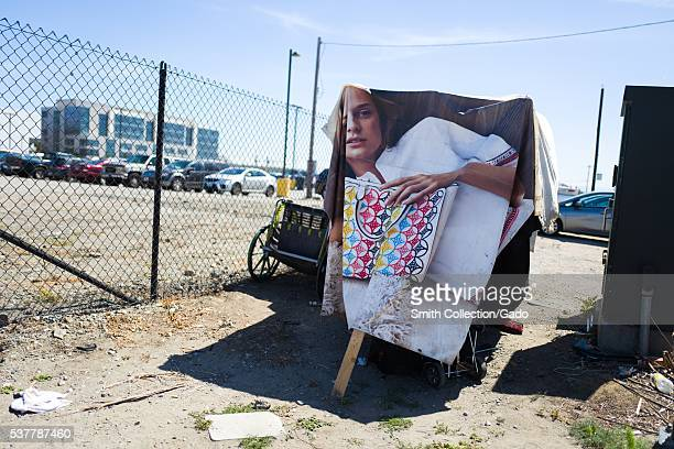 Homeless encampment built with materials including a poster of a female model holding a handbag in the Mission Bay neighborhood of San Francisco...