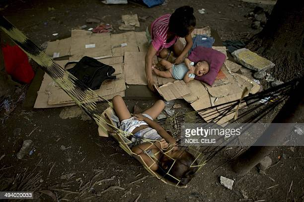 A homeless family rest in a public park in Manila on May 27 2014 Optimism is soaring that the Philippines is finally becoming an Asian tiger economy...