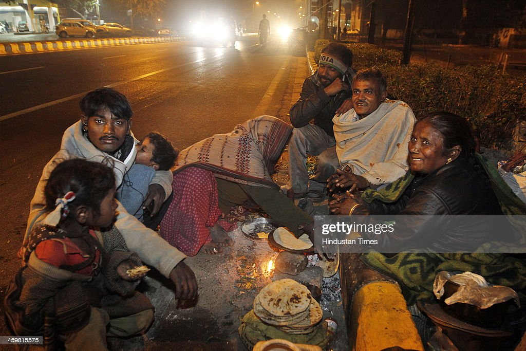 A homeless family that hails from Aligarh cooks dinner in open at Baba Khadak Singh Marg during chilly night on December 31, 2013 in New Delhi, India. Delhi Urban Development Minister, Manish Sisodia took a surprise inspection of the night shelters in the city to check the plight of the shivering poor. (Photo by Sanjeev Verma/Hindustan Times via