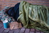 A homeless female veteran sleeping on the ground outside of a brick building with a sign begging for change.