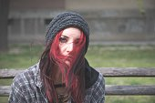 Homeless girl, Young beautiful red hair girl sitting alone outdoors with hat and shirt feeling anxious and depressed after she became a homeless person close up portrait