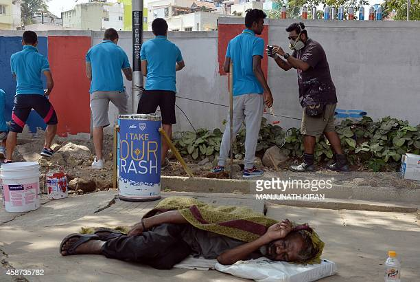 A homeless Indian sleeps on the footpath as Bengaluru Football Club players paint a wall in the neighbourhood of the football stadium in Bangalore on...