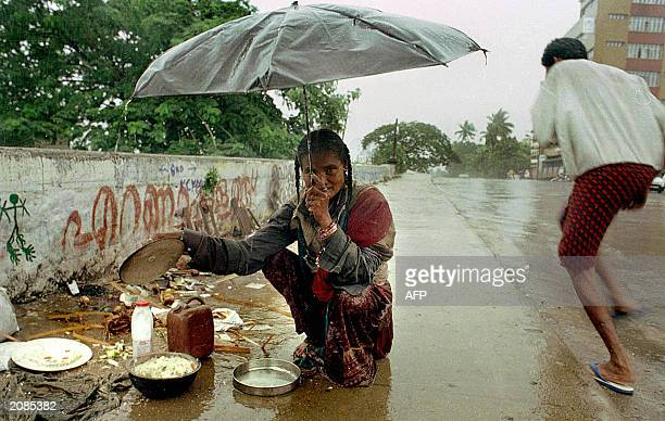 A homeless Indian woman puts her few belongings away from the rain in Kochin 06 June 2003 Rains which have begun drenching parts of northeast India...