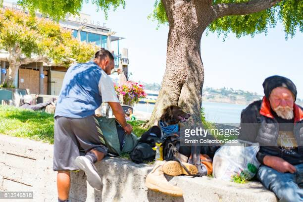 A homeless man and a traveler with a dog sit in Yee Tock Chee park on Bridgeway Road in the San Francisco Bay Area town of Sausalito California June...