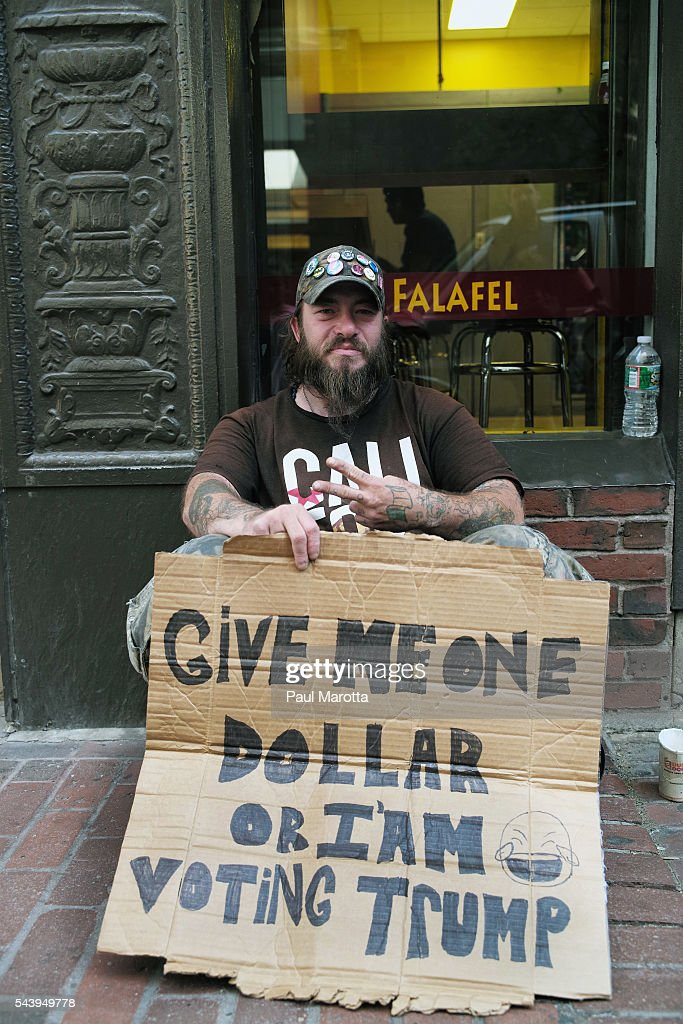 A homeless man asks for money to not vote for Donald Trump on June 30, 2016 in Boston, Massachusetts. His sign reads 'Give me one dollar or I'm voting Trump.'