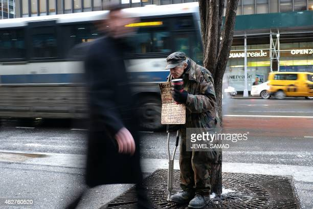 A homeless man begs for donations outside a subway station in New York on February 4 2015 New York may be famous abroad for glitz glamor and Park...