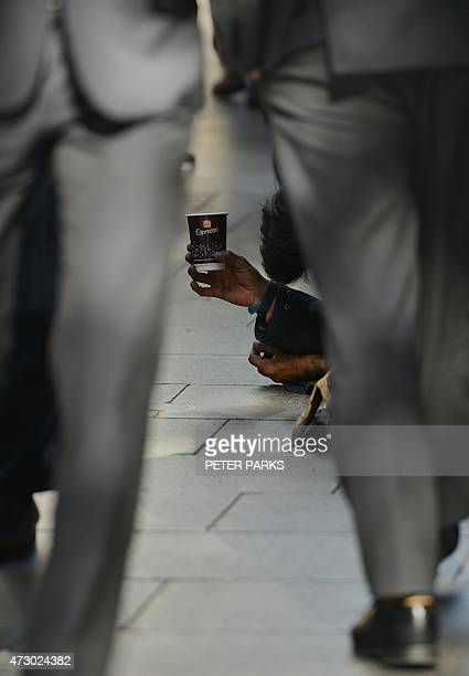 A homeless man begs for money on a street in the Central Business District of Sydney as the Australian government prepares to release its 2015/16...