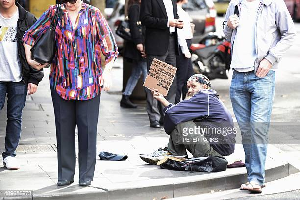 A homeless man begs on a street in Sydney on May 12 2014 Australia's first budget under conservative Prime Minister Tony Abbott to be released on May...