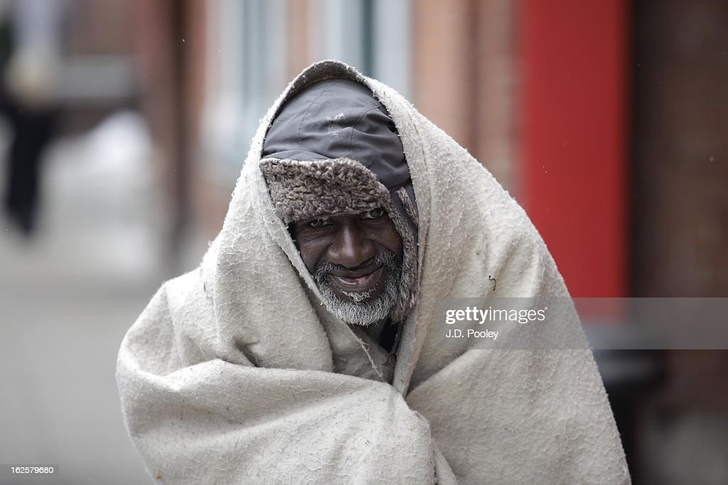 A homeless man covers himself from the cold while walking down a sidewalk February 24, 2013 in Detroit, Michigan. The city of Detroit has faced serious economic challenges in the past decade, with a shrinking population and tax base while trying to maintain essential services. A financial review team issued a finding on February 19 identifying the city as being under a 'financial emergency.' Michigan Gov. Rick Snyder has 30 days from the report's issuance to officially declare a financial emergency, which could result in the governor appointing an emergency financial manager to oversee Detroit's municipal government.