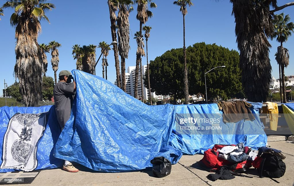 A homeless man fixes his tent along a street in Los Angeles, California on February 9, 2016. Los Angeles City and County officials are voting February 9 on plans aimed at ending homelessness in the community, mostly by making permanent housing available to the tens of thousands of people who are homeless. Frederic J. BROWN