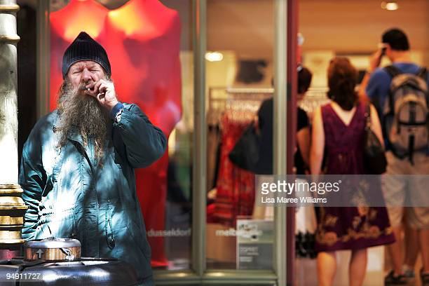 A homeless man has a cigarette outside a retail store in Pitt Street Mall during the Christmas shopping period on December 19 2009 in Sydney...