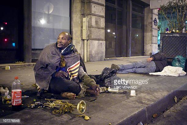 A homeless man heats up his feet above a ventilation grille as an other sleeps in a street of Paris on December 3 as France shivers under freezing...