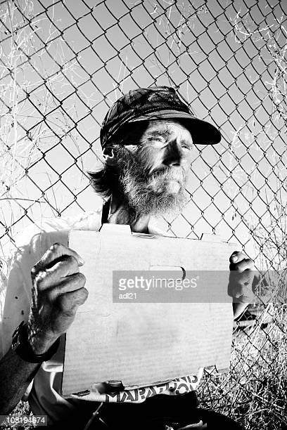 Homeless Man Holding Blank Sign Sitting Against Fence