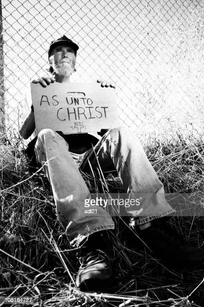 Homeless Man Holding Sign 'As Unto Christ', Black and White