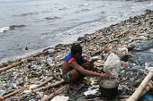 A homeless man holds a milk fish caught just a few meters from the shore while cooking lunch along the garbage ridden shore of Manila Bay in Roxas...