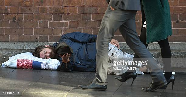 A homeless man holds out his cap for money in Sydney's Central Business District on July 10 as Australia's unemployment rate returned to a decade...