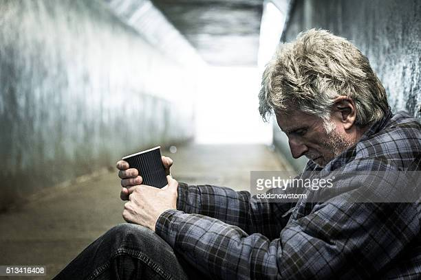 Homeless man in subway tunnel begging with paper cup