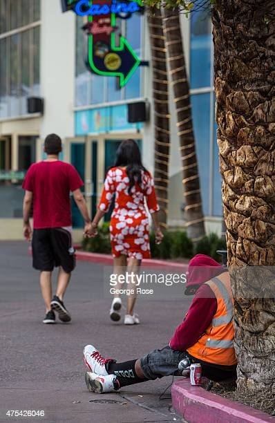 A homeless man is passed out on the Las Vegas Strip in front of the Flamingo Las Vegas on May 19 2015 in Las Vegas Nevada Tourism in America's 'Sin...