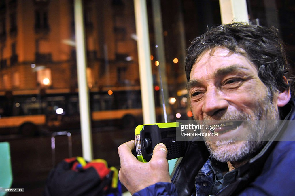 A homeless man listens to a radio distribued by members of the Association 'Les Enfants du Canal', in a street in Paris, on December 21, 2012. Thousands of radios will be distributed to the homeless in the streets of Paris from December 21 to 24 to 'break their isolation' and give them access to information and culture. This initiative named '1000 radios' is funded 70% by the non-profit 'Fondation de France', as part of its project 'Christmas Eves of Solidarity'.
