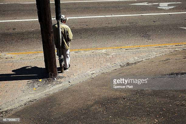 A homeless man looks for donations along a highway entrance on March 28 2015 in Corpus Christi Texas Texas which in just the last five years has...