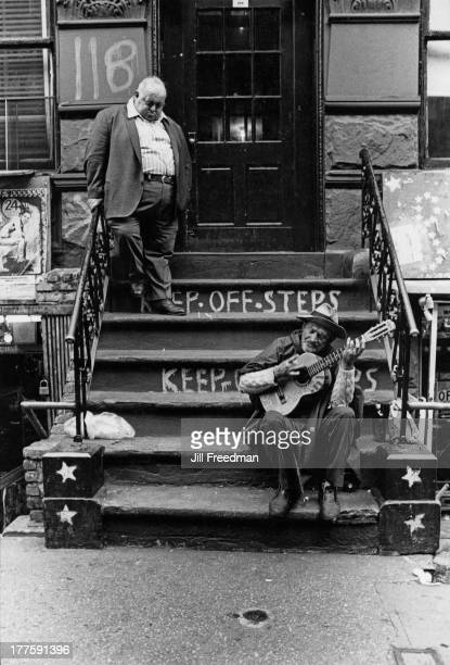 A homeless man plays a small guitar on the steps of an apartment block on MacDougal Street Greenwich Village New York City 1972