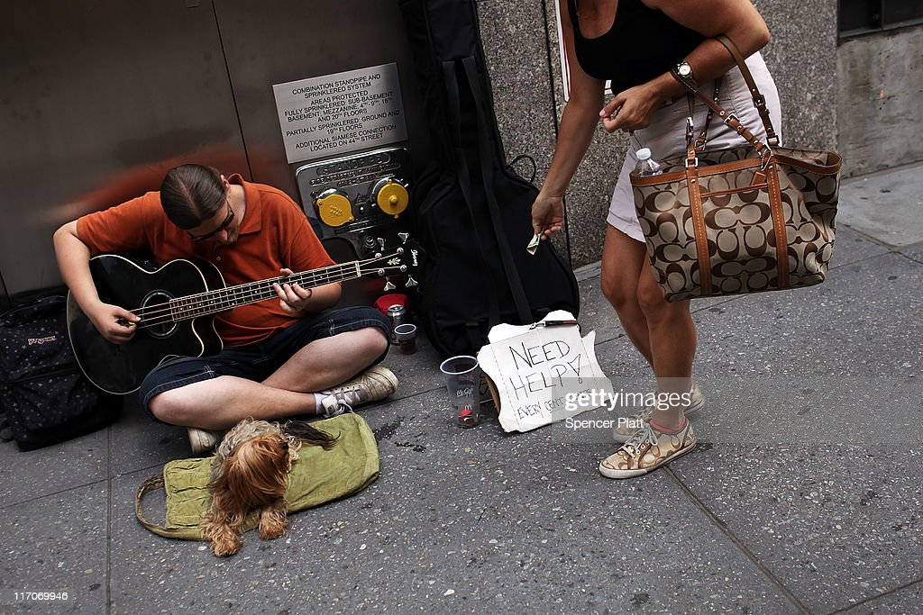 A homeless man plays his guitar while panhandling on the street on June 20, 2011 in New York City. According to an annual report on the city's homeless population conducted by the Coalition for the Homeless, a record 113,553 people turned to shelters last year. This was an eight percent increase over the previous year and is a 37 percent increase since 2002. While the reasons for the increase are numerous, the economy and the unemployment rate played a significant part in the numbers.