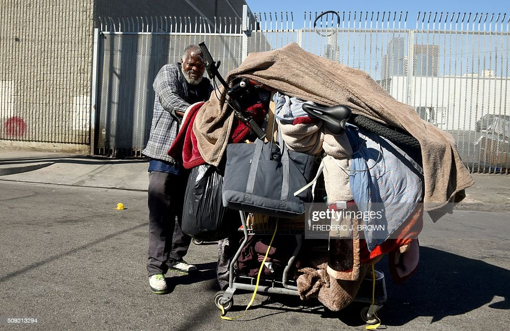 A homeless man pushes his cart of belongings along a street in Los Angeles, California on February 9, 2016. Los Angeles City and County officials are voting February 9 on plans aimed at ending homelessness in the community, mostly by making permanent housing available to the tens of thousands of people who are homeless. Frederic J. BROWN