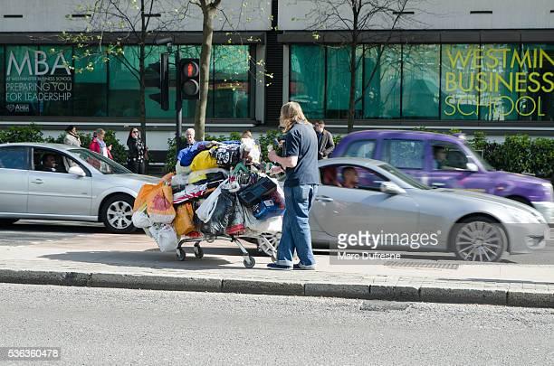 Obdachlos Mann schieben einem Einkaufswagen voller Einkaufstüten