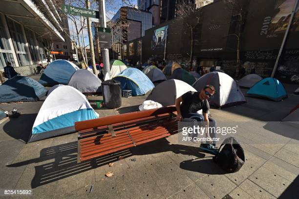 A homeless man puts his shoes on after getting out of his tent set up in Martin Place which has become known as 'Tent City' as homeless people set up...