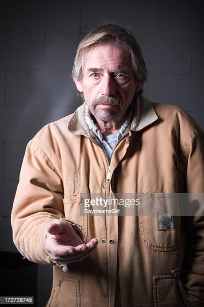 Homeless Man Reaching with Hand Outstretched Looking at Camera
