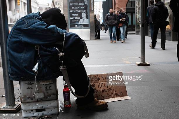 A homeless man rests on the street on December 21 2015 in New York City On Monday the homeless advocacy group Picture the Homeless joined supporters...