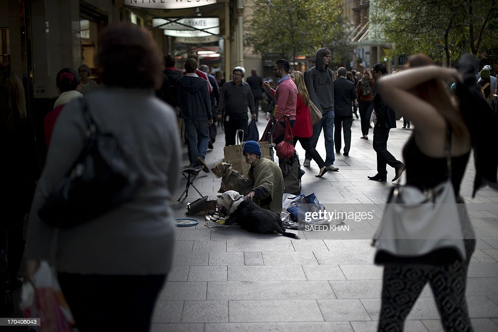 A homeless man seeks financial help while sitting with his pets in the central business district of Sydney on June 13, 2013. Australia's unemployment rate eased to 5.5 percent in May, an unexpected fall that could see the central bank hold off on cutting interest rates next month. AFP PHOTO / Saeed KHAN