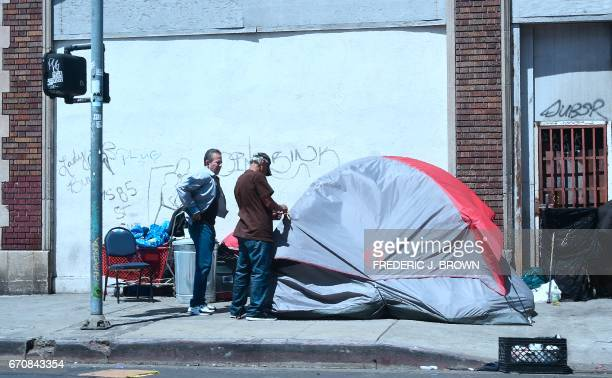 A homeless man sets up his tent at a street corner in downtown Los Angeles California on April 20 where the city's mayor Eric Garcetti is proposing...