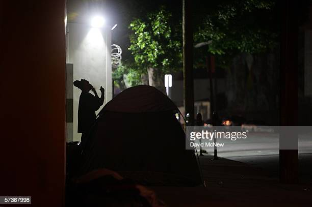A homeless man shaves at his encampment on a downtown sidewalk in the early morning hours of April 19 2006 in Los Angeles California Most homeless...