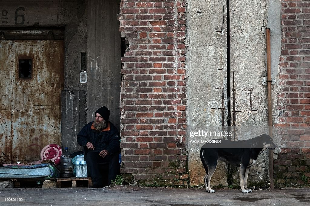 A homeless man sits at his makeshift shelter at Greece's main harbour Piraeus port near Athens, on February 6, 2013.