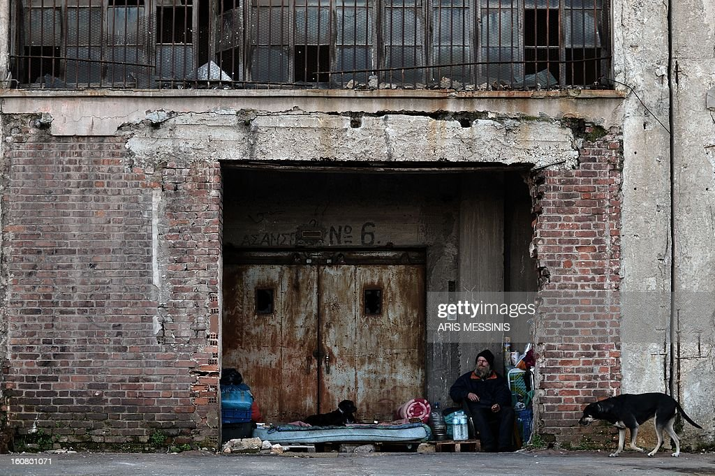 A homeless man sits at his makeshift shelter at the Greece's main harbour Piraeus port, near Athens, on February 6, 2013.