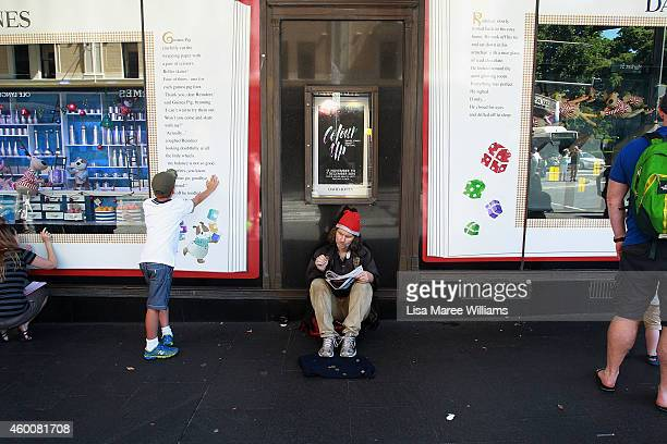 A homeless man sits between Christmas window displays on December 7 2014 in Sydney Australia