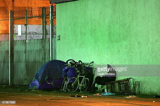 A homeless man sits by his possessions at his encampment on a downtown sidewalk in the early morning hours of April 19 2006 in Los Angeles California...